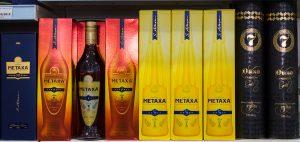 scaffale con bottiglie di metaxa da acquistare durante le vacanze in grecia